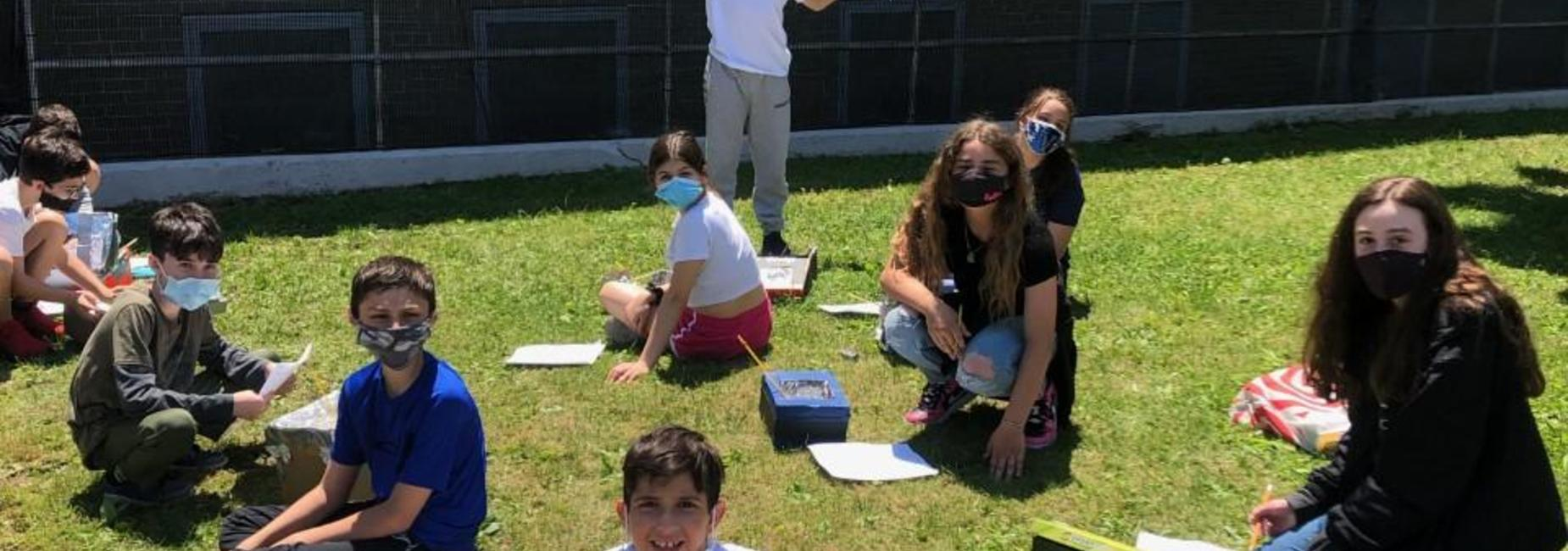 Students learning on the lawn at IS 7