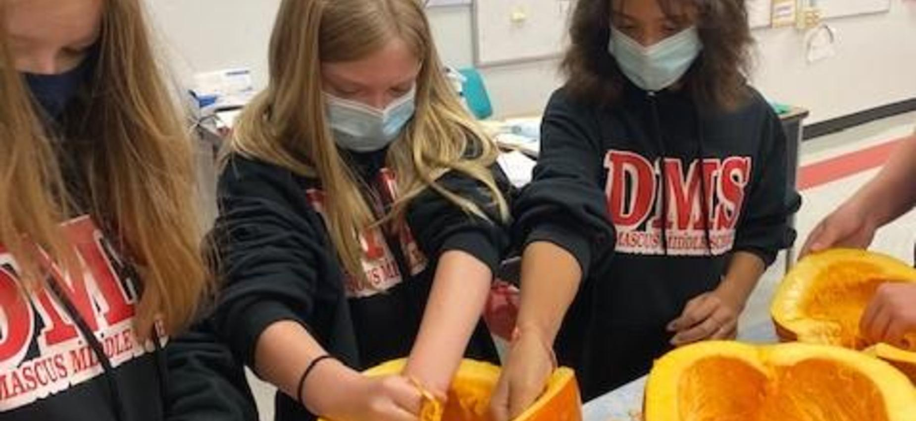Students clean out a pumpkin in a classroom.