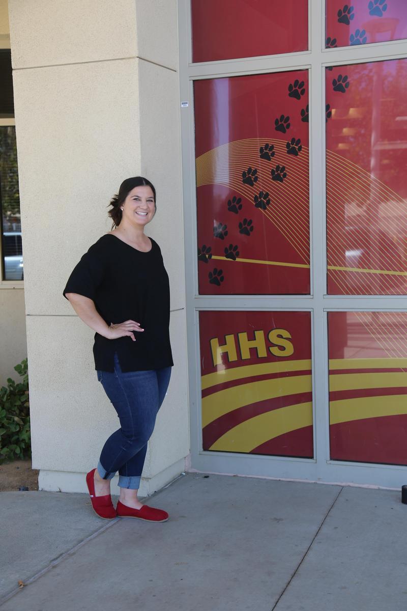 Lindsay Brown standing in front of a Hemet High School sign.