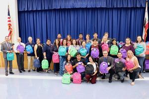 Volunteer group posing with backpacks