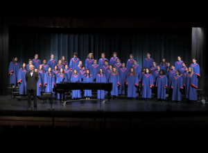 STUDENTS IN RED-TRIMMED BLUE CHOIR ROBES STANDING ON RISERS ON A DARKENED STAGE.