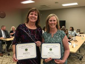 A photo of Cheryl Geisler and Angie Isgro holding their certificates after graduating from EMIS training