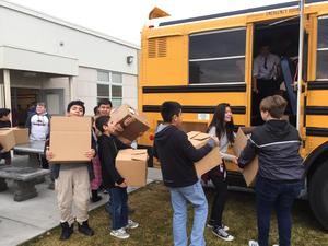 Students bringing canned food to the bus.