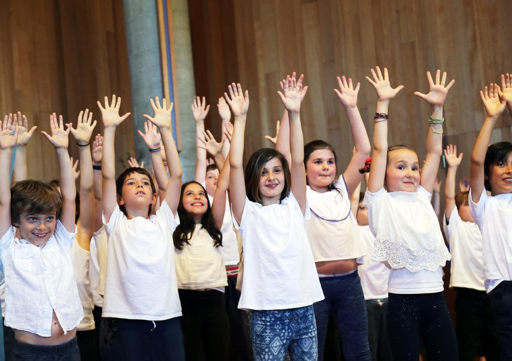 A group of children stand on a stage. They are all wearing white shirts and they have their hands in the air with spread fingers.
