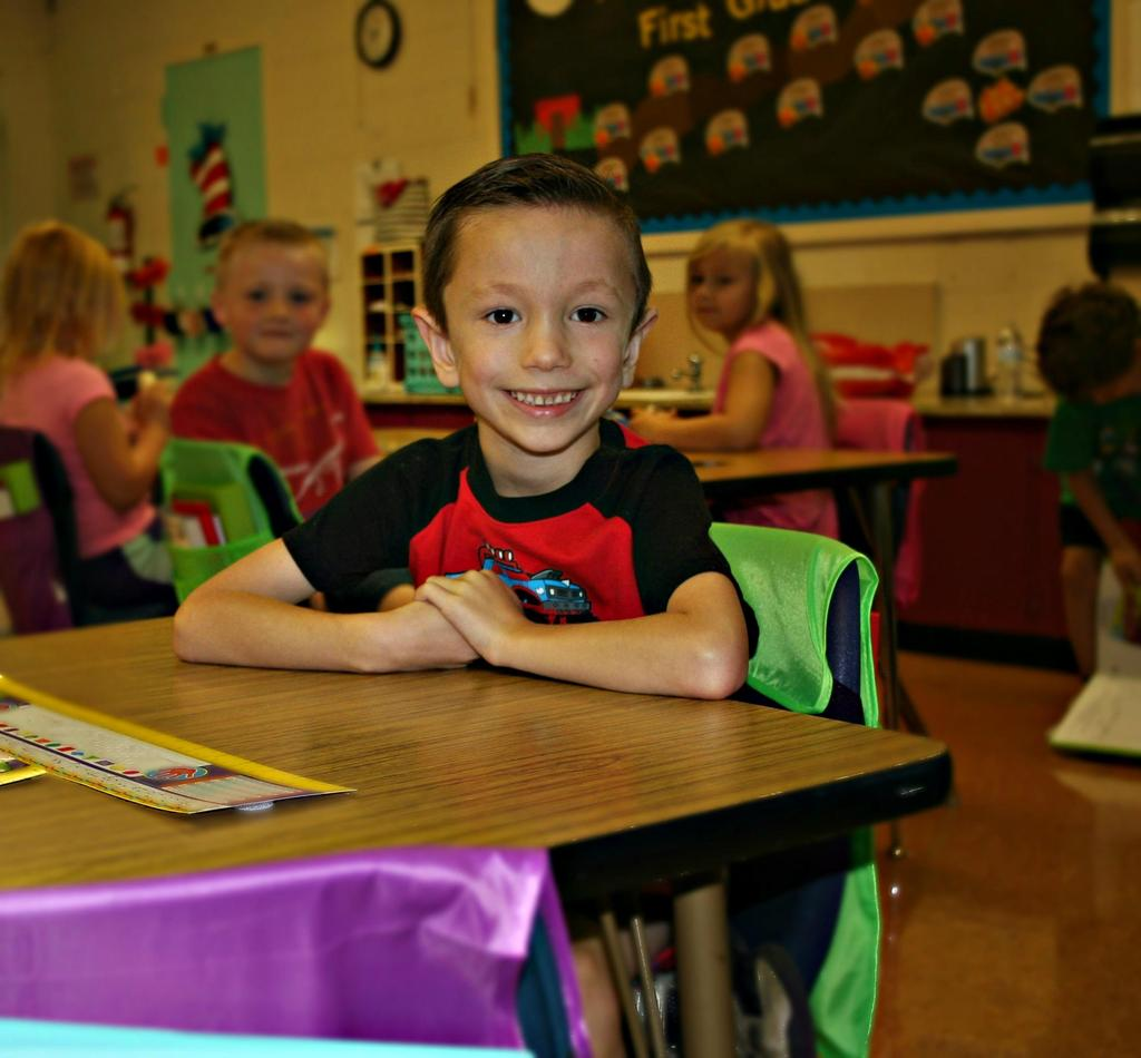 Boy smiles from his desk on the first day of school at Mt. Pleasant Elementary.