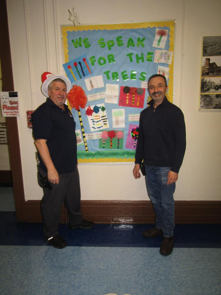 males staff posing by seuss bulletin board