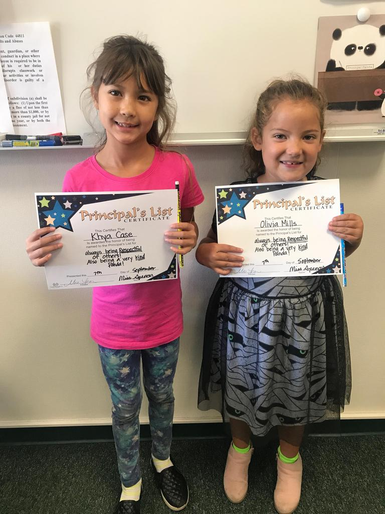 Two girls receiving a Principal's award