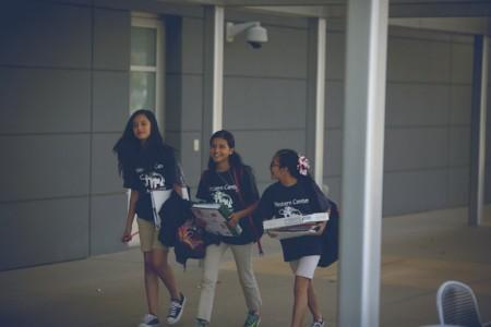 Three female students walking and laughing