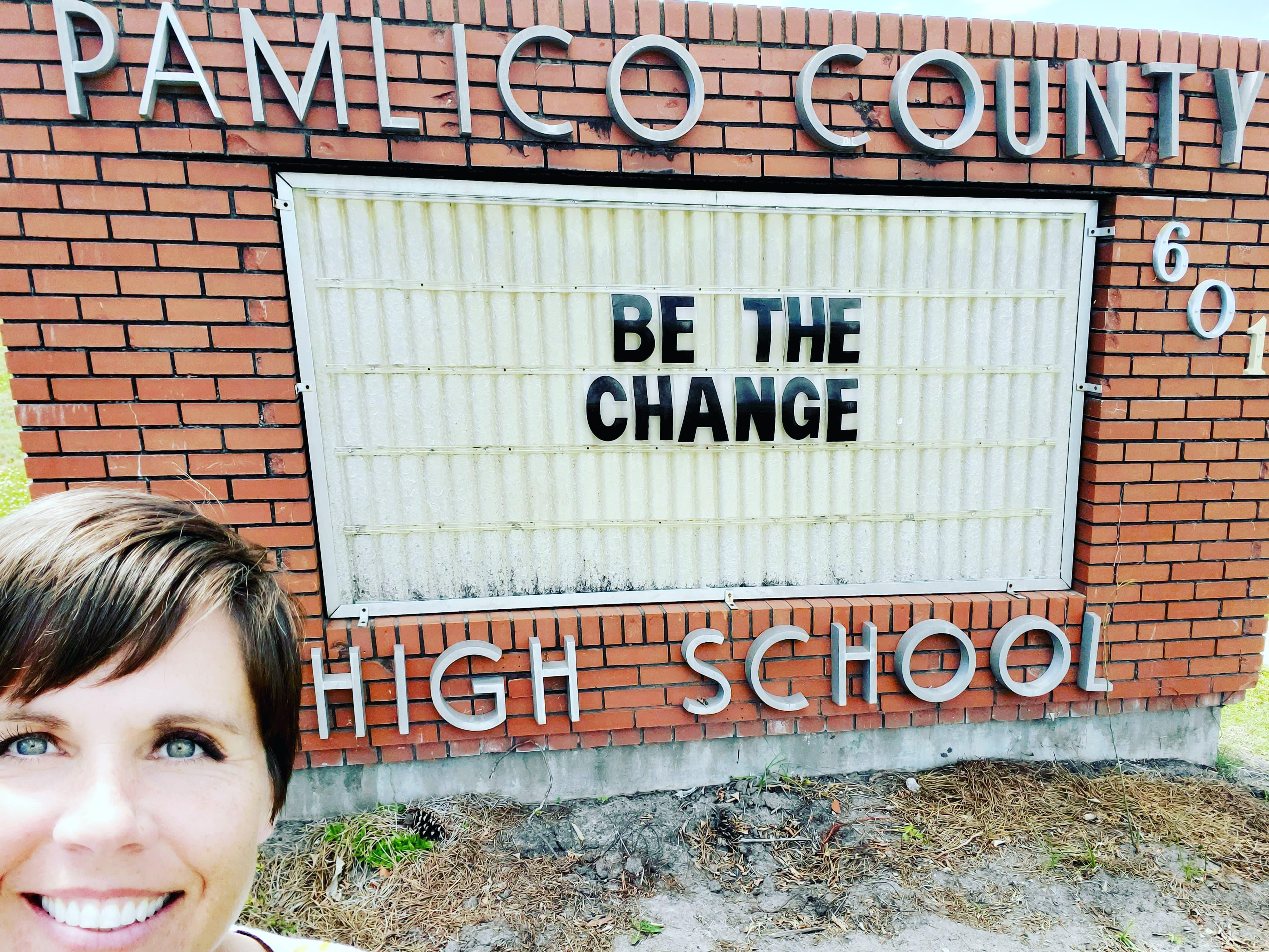 Principal Holton in front of the PCHS sign, which reads
