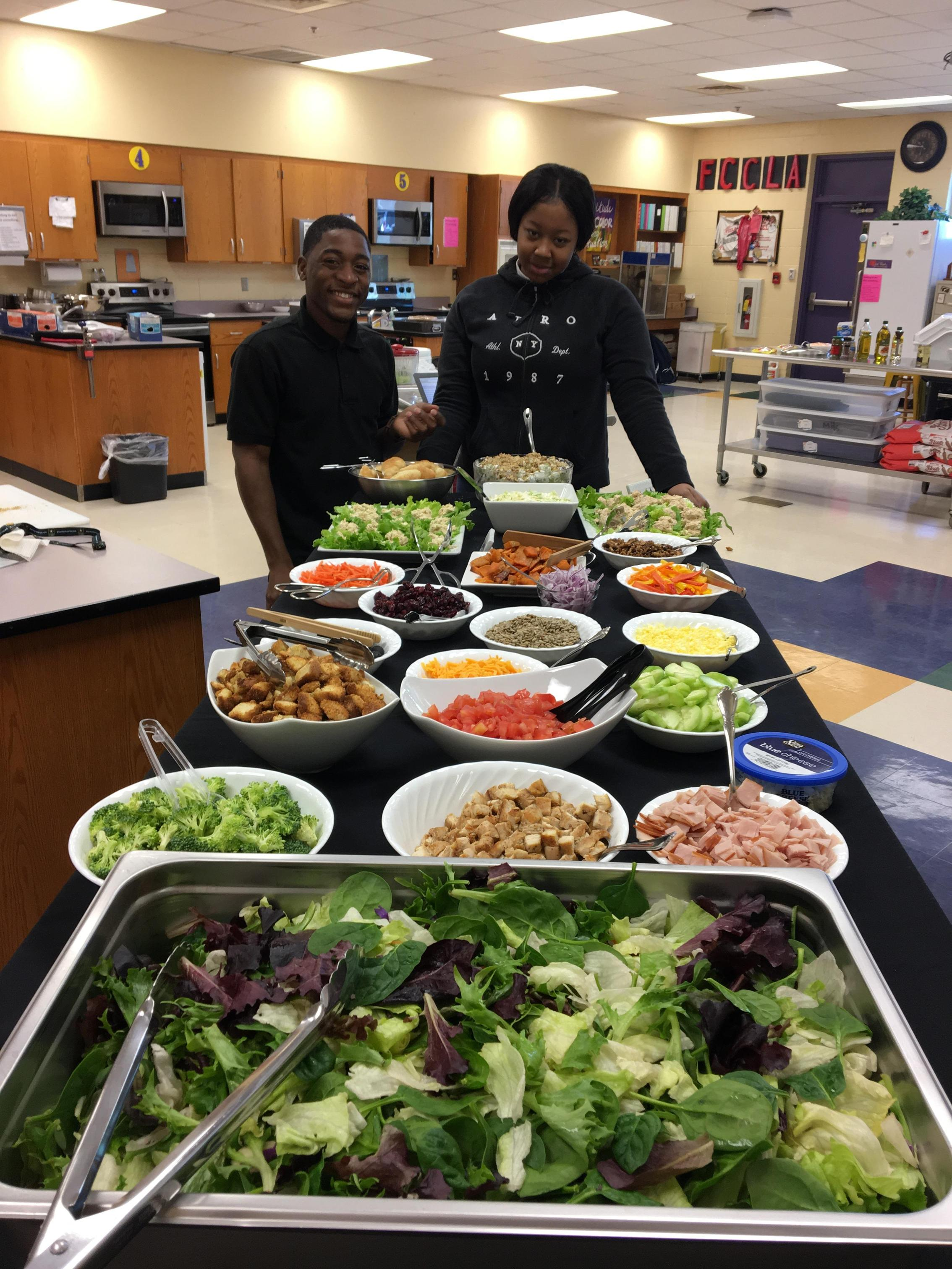Beautiful arrangement of salad toppings and 3 students in black chef coats.