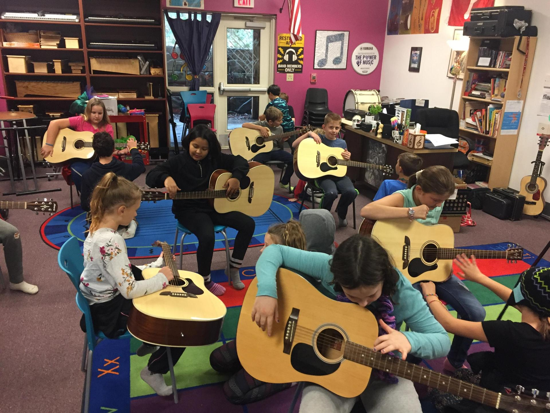Fifth graders learn guitar.
