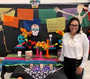 Sonia Martinez de la Rocha standing in front of school artwork.