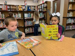 two kindergarten student reading in library