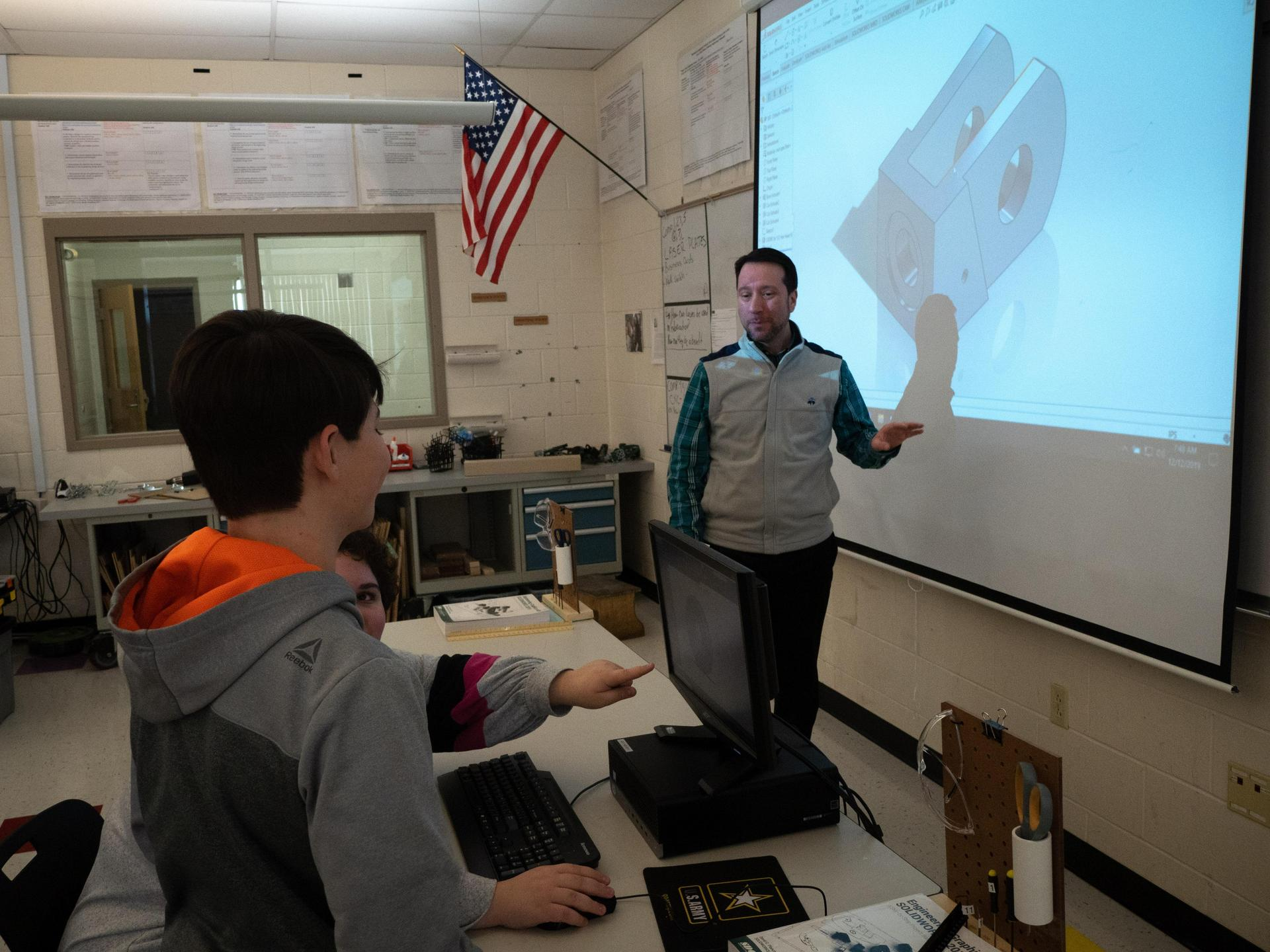 Mr. Xydias in front of projector screen showing a 3D model