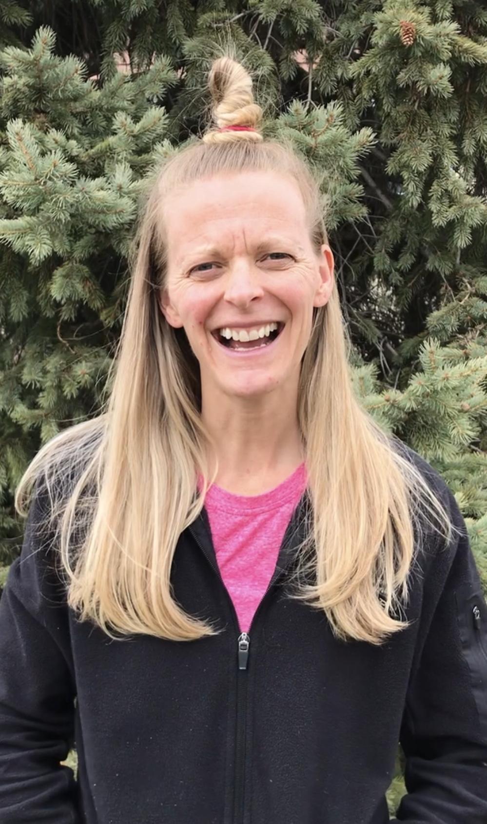A teacher smiles with crazy hair