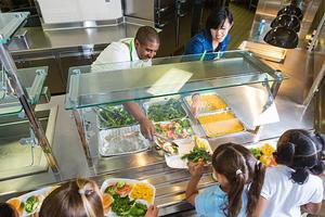 School staff members serves students lunch from salad bar