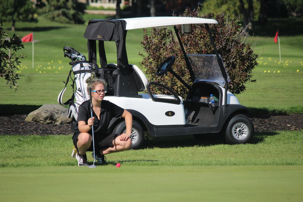 A female golfer studying the green.