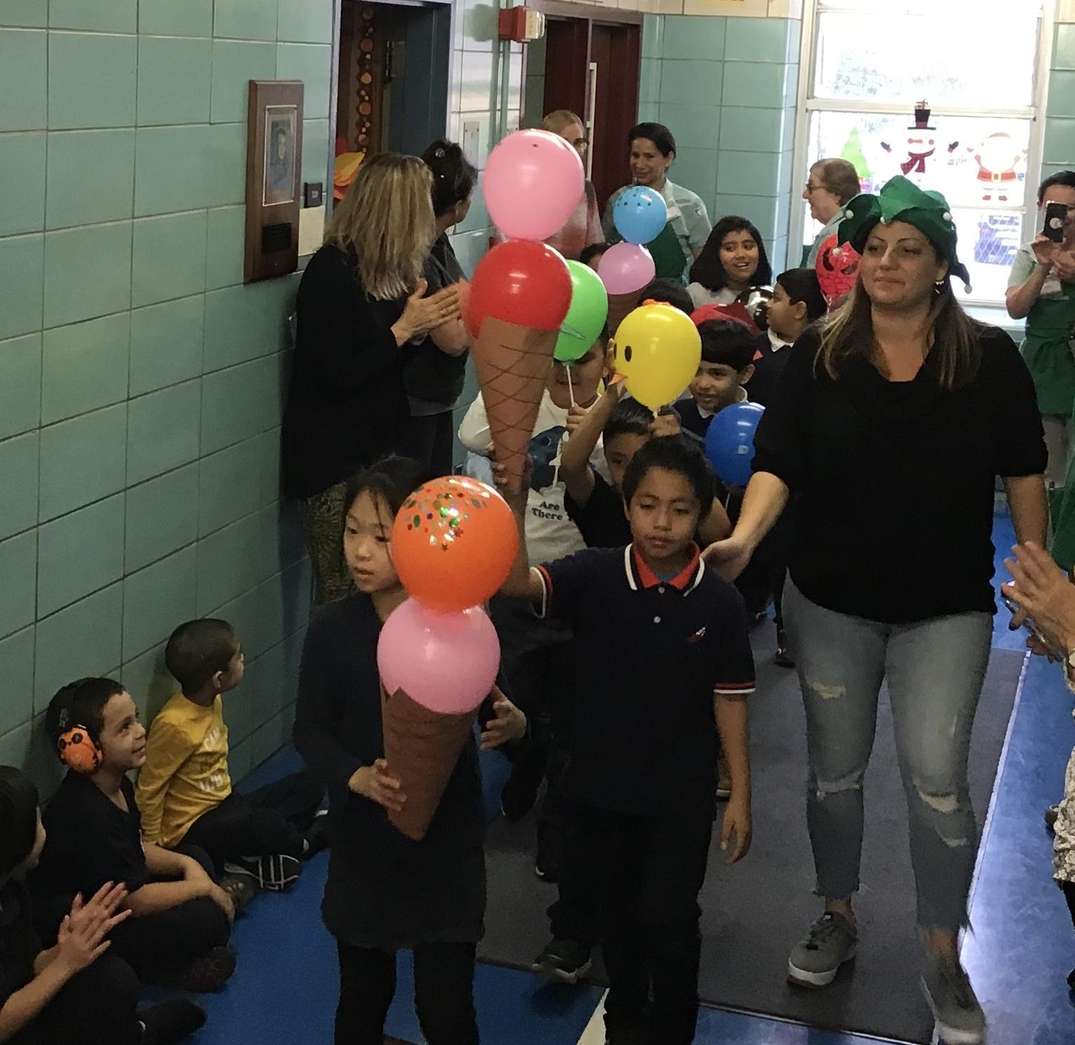 students and teachers parading in school hallway with balloons
