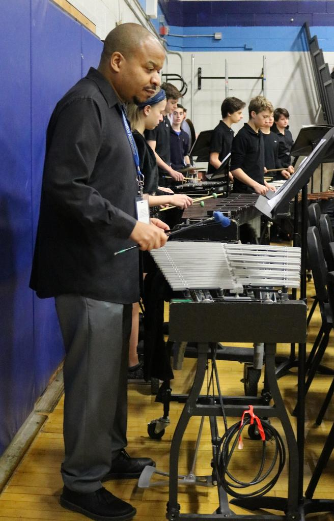 Photo of music teacher joining 8th grade band in performing patriotic tunes during Veterans Day Assembly.