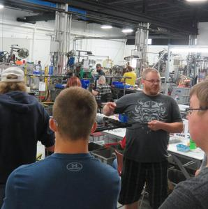 An engineer talks with students about his job at H & L Manufacturing in Middleville.