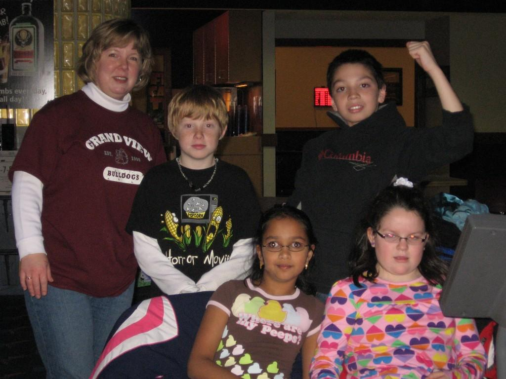 students pose for camera at bowling alley with chaperone