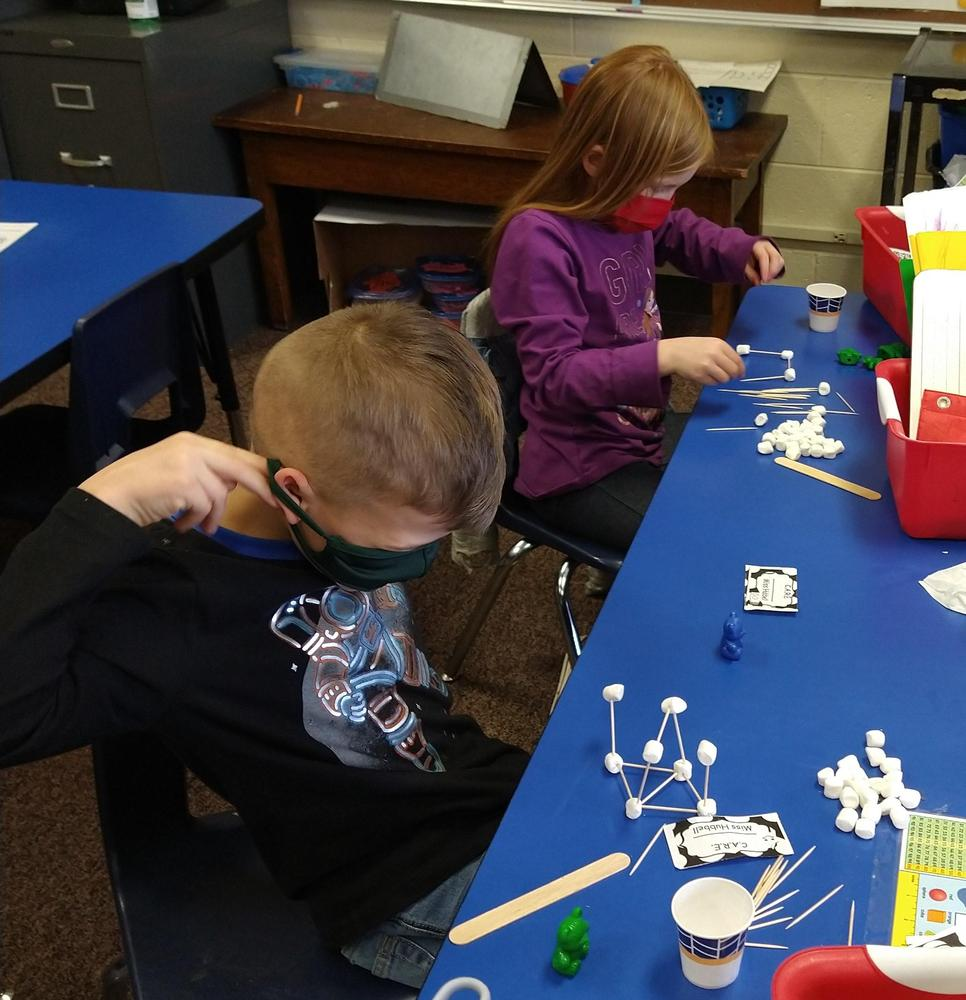 children building marshmallow towers