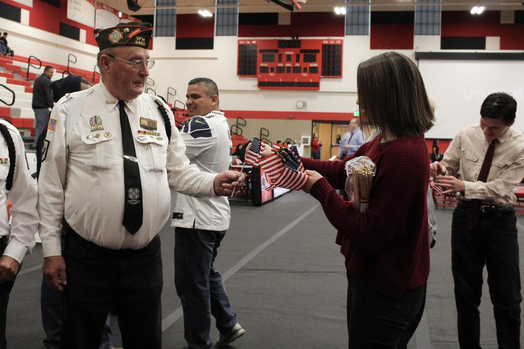 Picture of student giving veteran an american flag