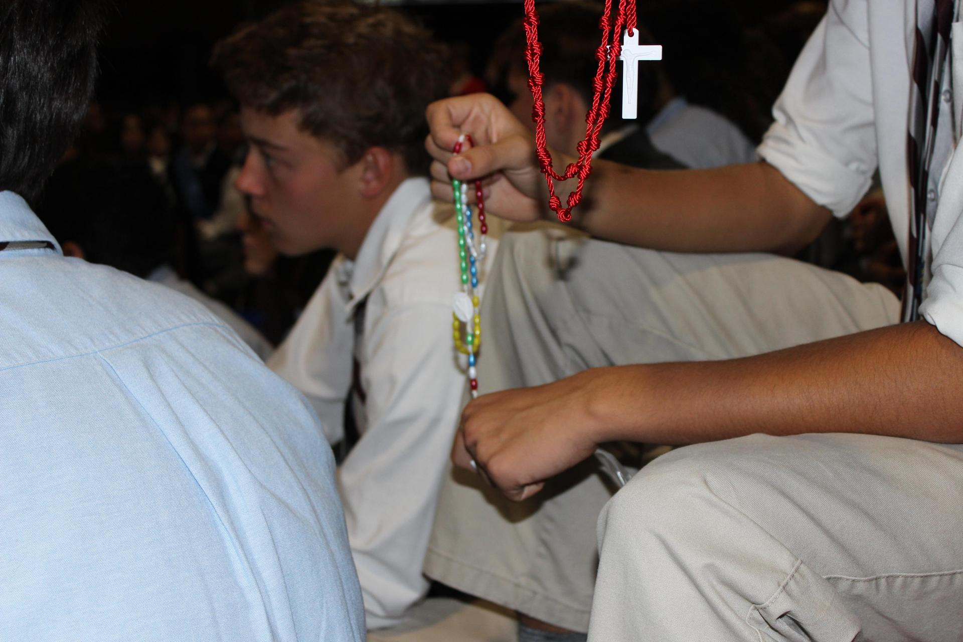 student holding rosary