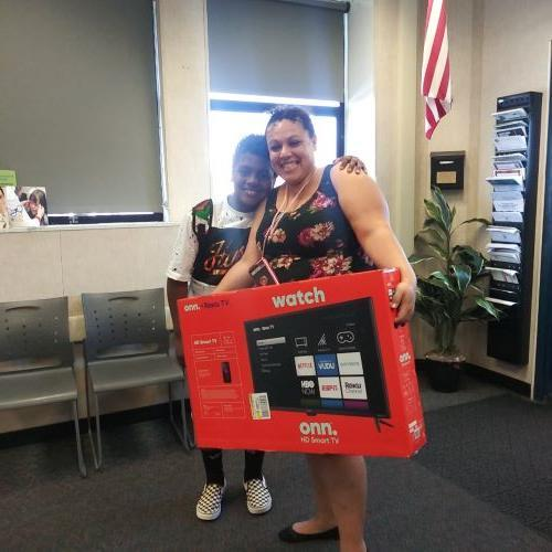 Attendance raffle winner happily posing with his mom with his new tv.