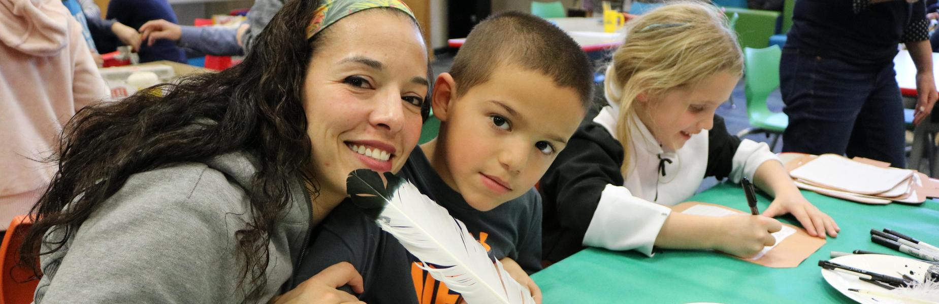 Mother and son pose for a picture as 2nd graders at Wilson School try their hands at colonial era crafts.