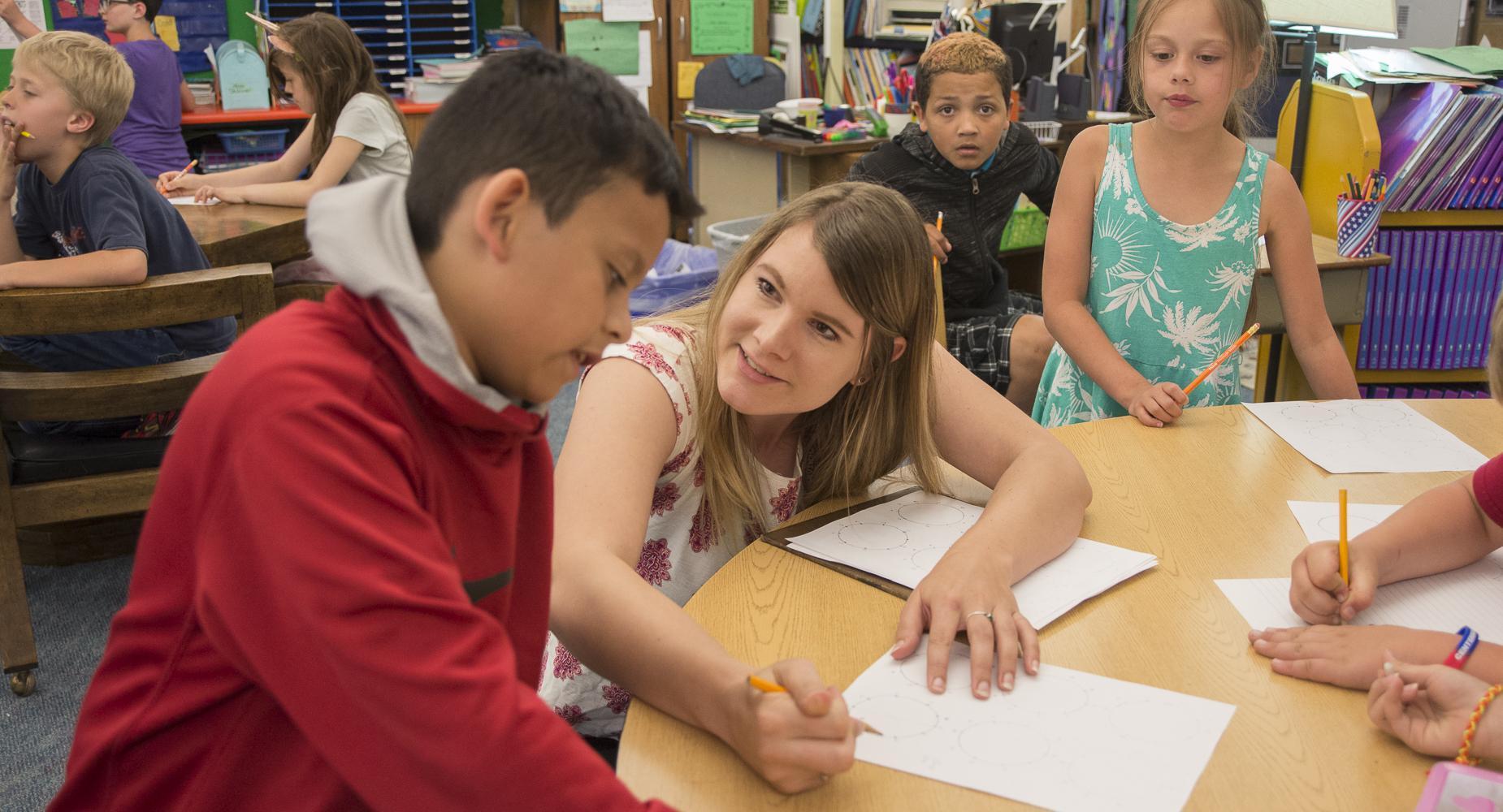 Teacher helps boy in red sweatshirt with worksheet.