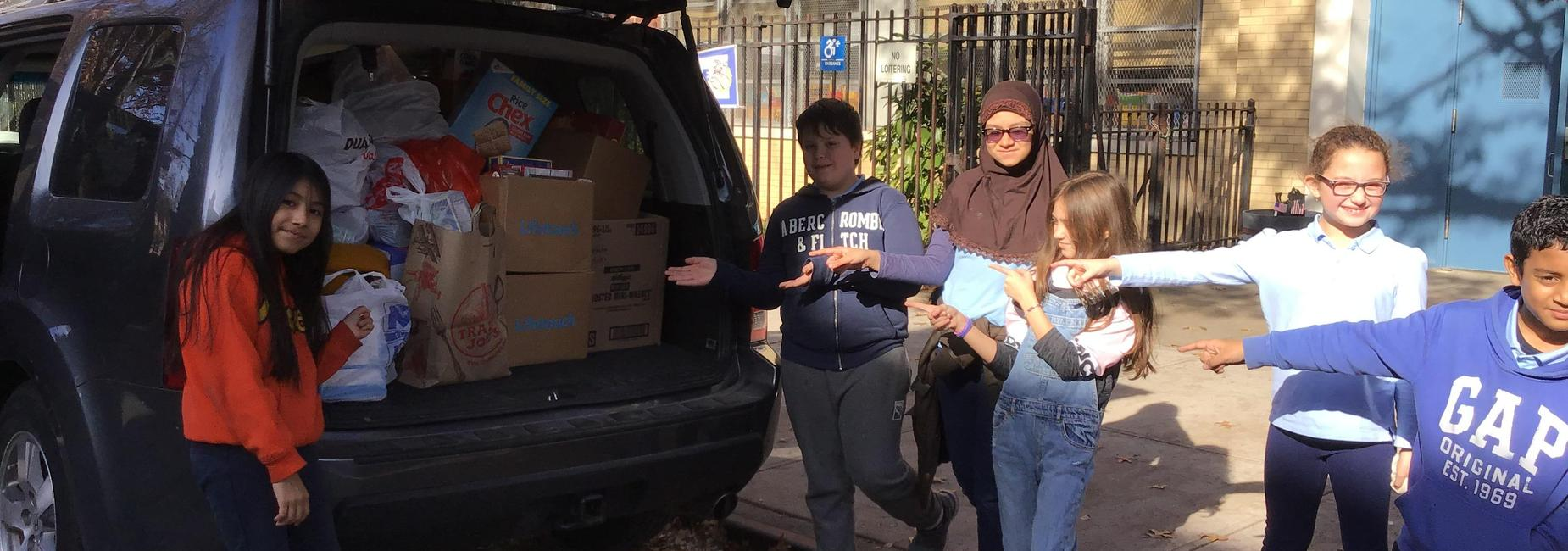 Students point at van full of donated food