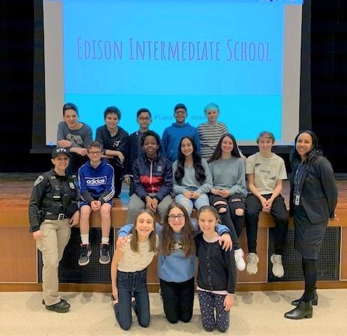 """Edison School Resource Officer Tiffany Kenny (left) and Assistant Principal Crystal Marsh (right) pose with students at a """"No Place for Hate"""" assembly in February."""