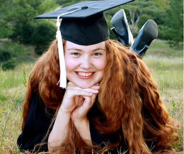 Female graduate lying in field with chin in hands.