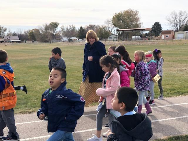 Dr. Kellerer walks with children at school