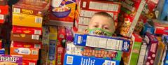 A mountain of cereal boxes surrounds kindergarten student Deegan Clark