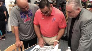 Author Roberto Rocha (right) looks through his 1986 Edinburg High School yearbook with former classmates ECISD School Board President Robert Pena Jr. (center) and Edinburg High School Head Football Coach J.J. Leija (left).