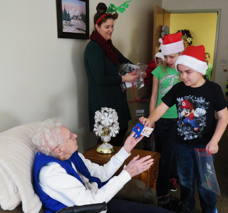 A Page Elementary students gives a handmade ornament to a Carveth Village resident.