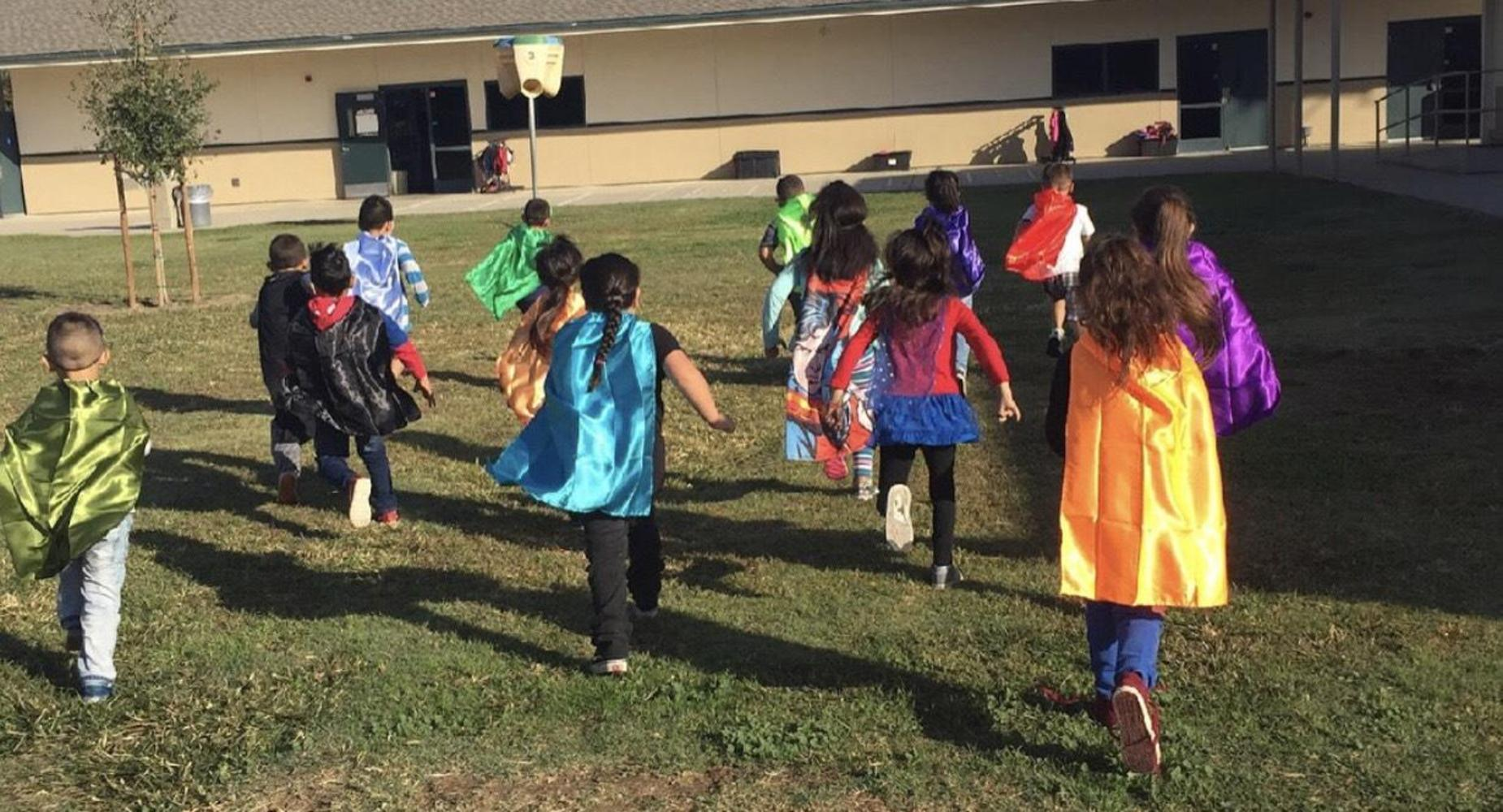 Students dressed as superheroes running across the grass.