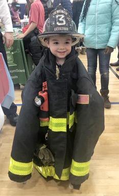 A young student wears a large fireman's uniform and helmet