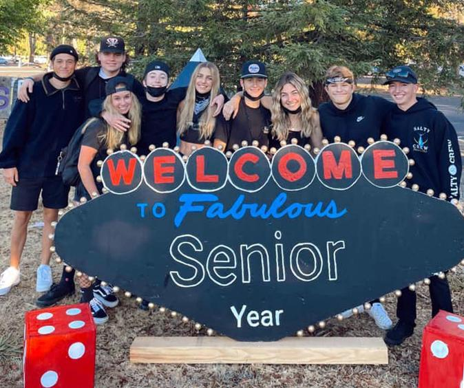 uhs seniors dressed in black in front of a sighn they made that looks like the las vegas welcome sign but has welcome to senior year instead of welcome to las vegas