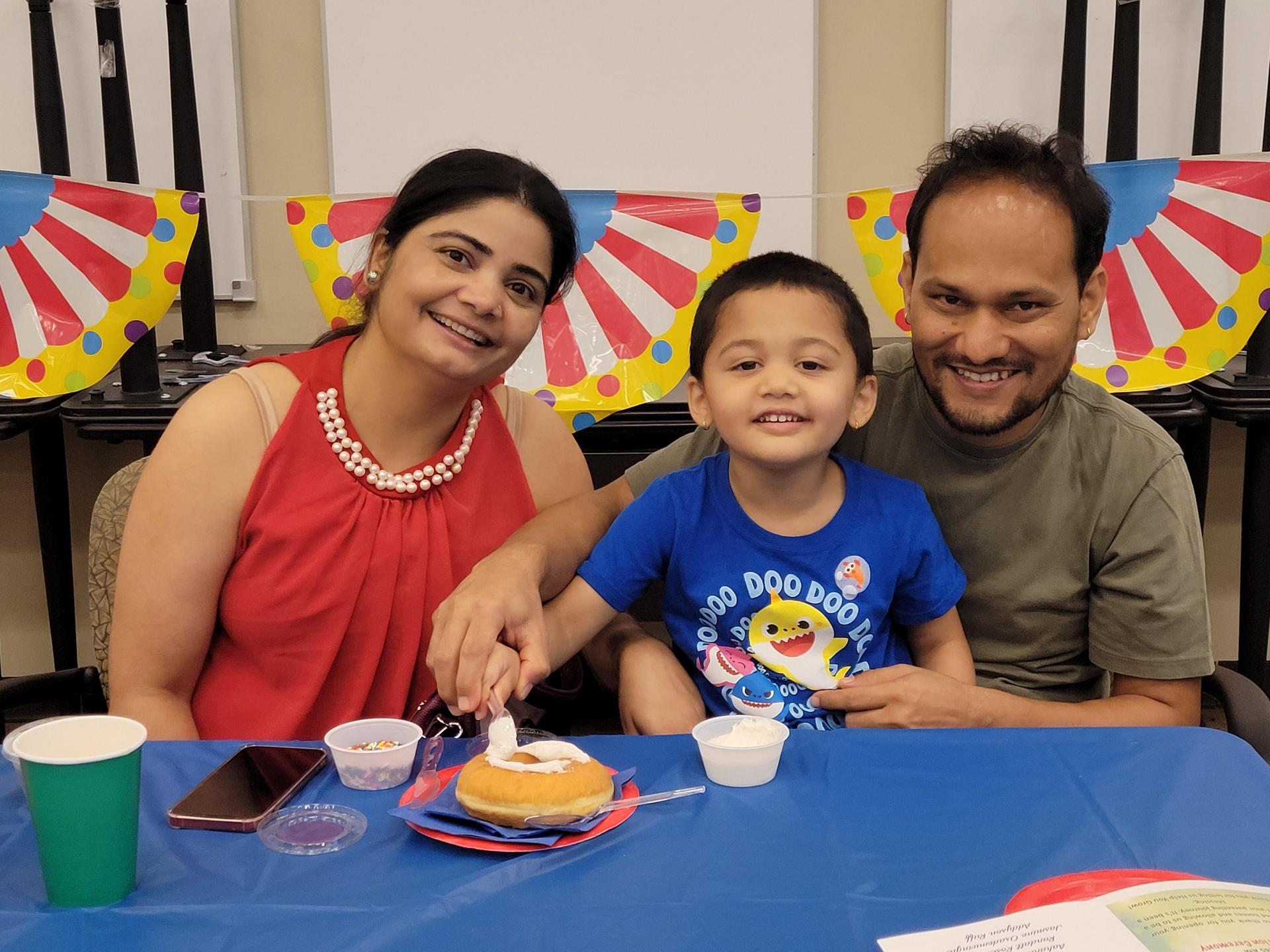 Parents and their child crafting snacks at the 2021 Help Me Grow/Every Child Succeeds graduation celebration