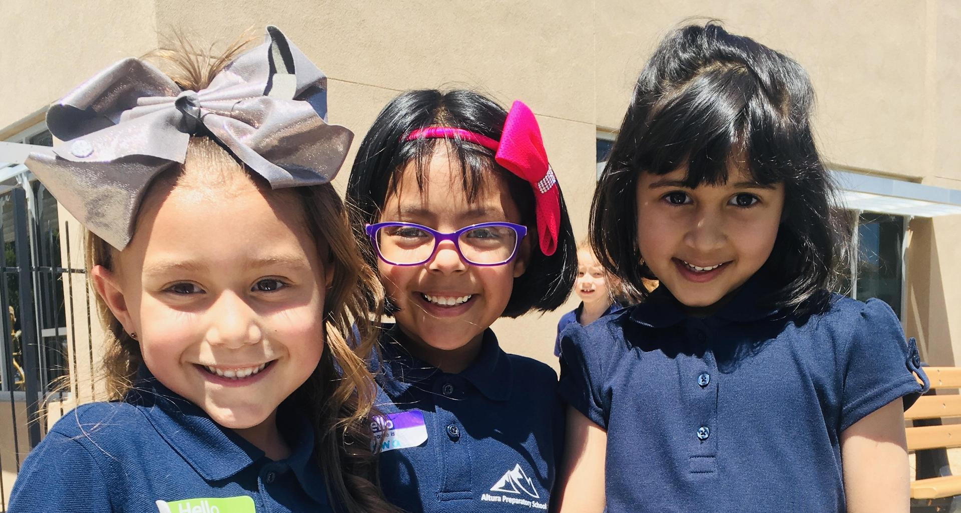 Students smile in their uniforms.