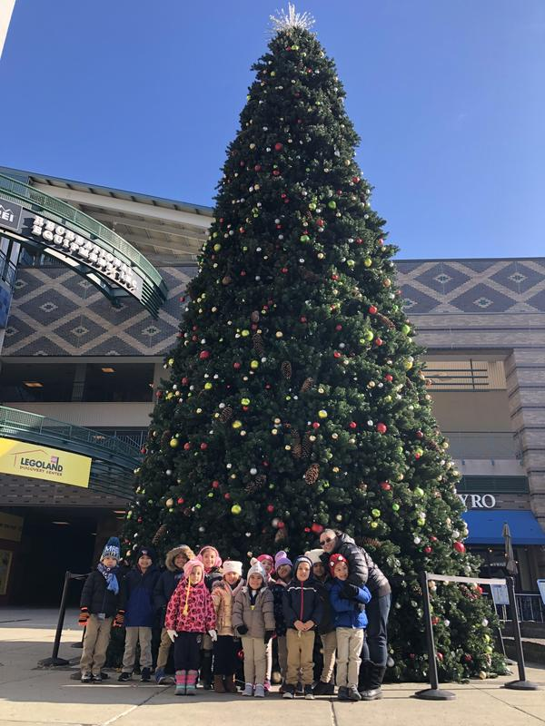 Ms. Ortiz class in front of a giant decorated christmas tree