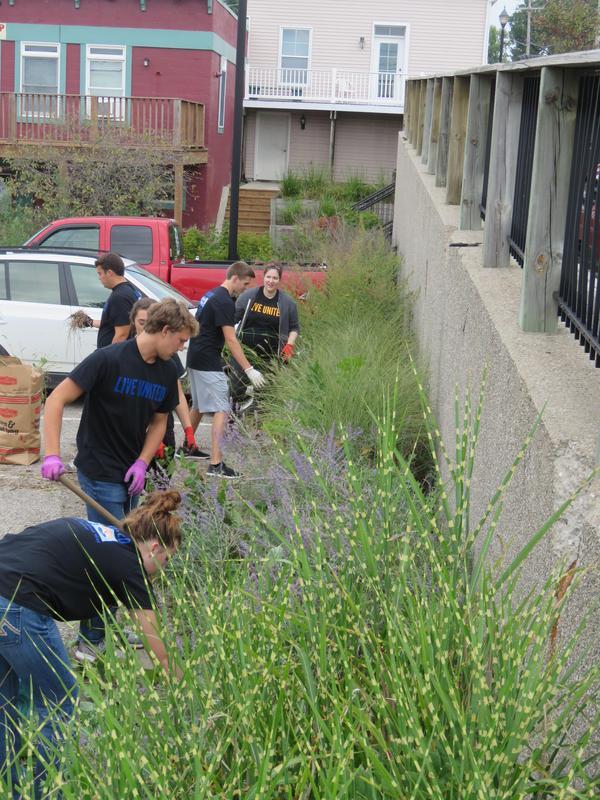 Students help clean up around the village.