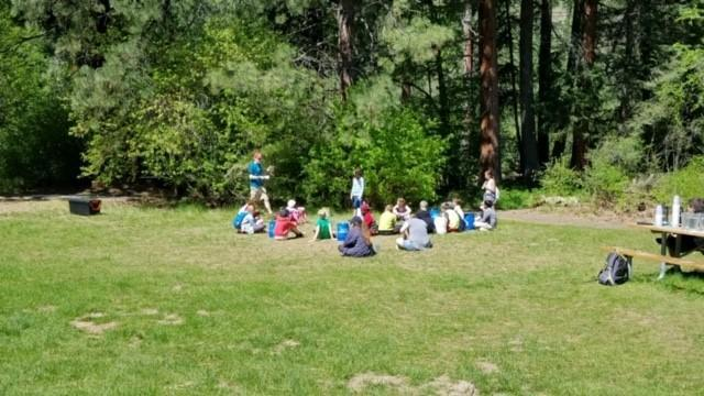 students sitting on the grass listening to a teacher talk