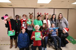 Group of students in holiday outfits looking at camera, smiling