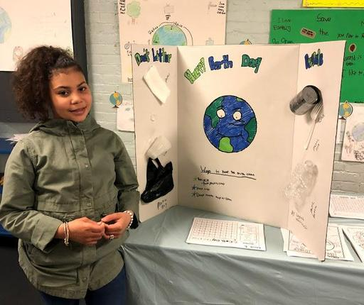Student standing to the right of her Earth Day Project