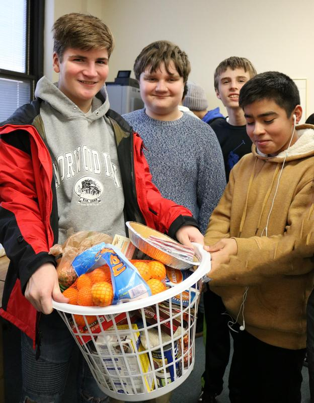 Westfield High School students prepare gift baskets for 4 refugee families who will enjoy a traditional Thanksgiving feast for the first time.  Pictured here are four WHS students displaying basket full of food.