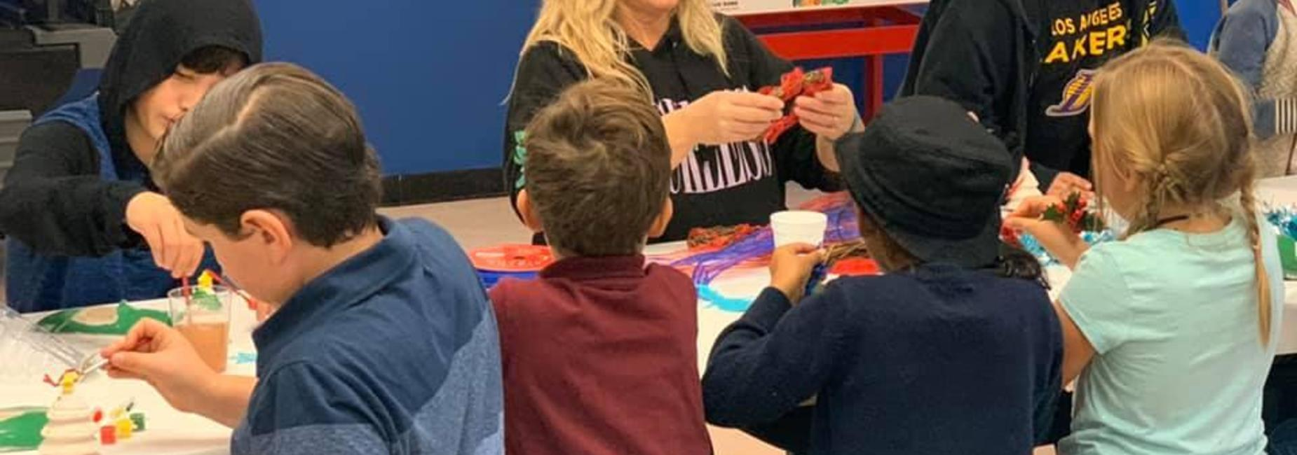 Hamilton K-8 families making Winter Crafts. Various children are painting Christmas trees  and using ribbon to make wreaths.